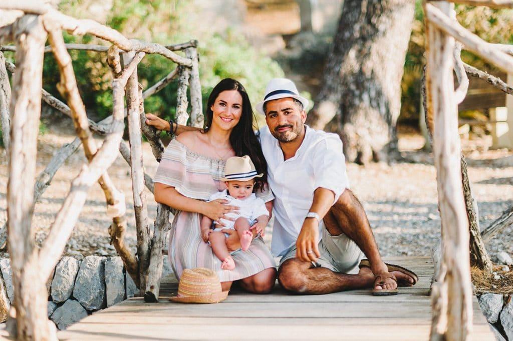 Familie mit Kind sitzt auf einer kleinen Holzbrücke