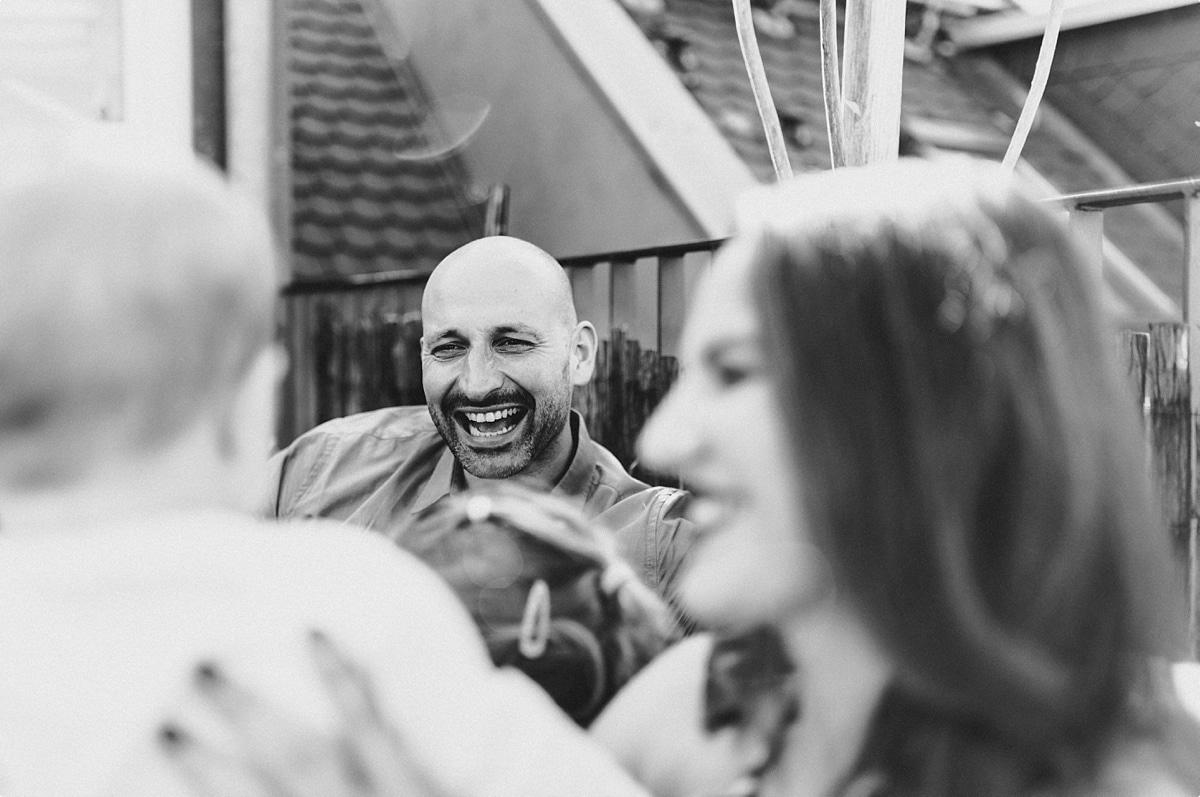 Familie sitzt auf der Terrasse und lacht herzlich in schwarz weiß