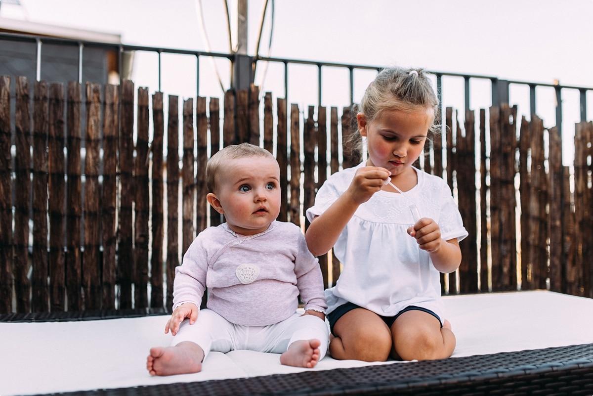 Tochter und kleines Baby sitzen gemeinsam auf der Terrasse