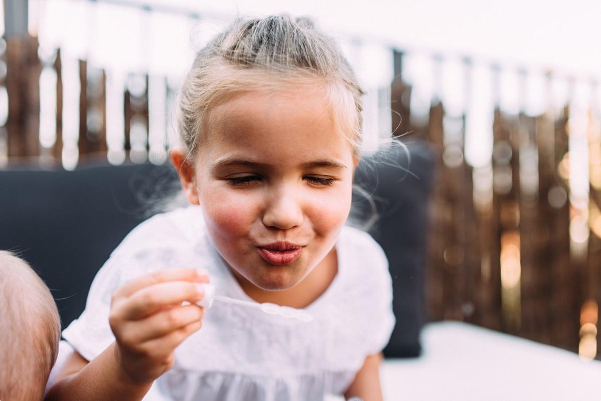 kleines Mädchen macht Seifenblasen auf der Terrasse