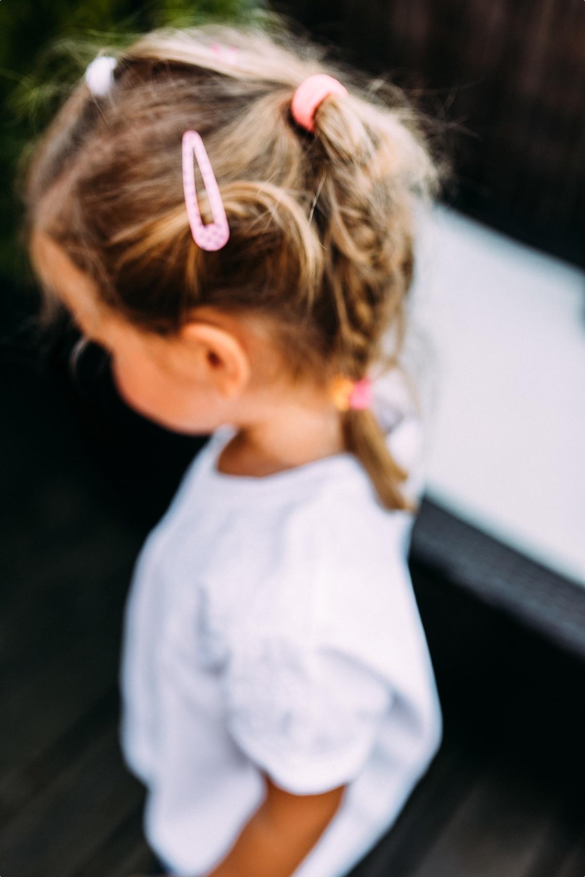 kleines Mädchen mit langem Haar und Haarspange