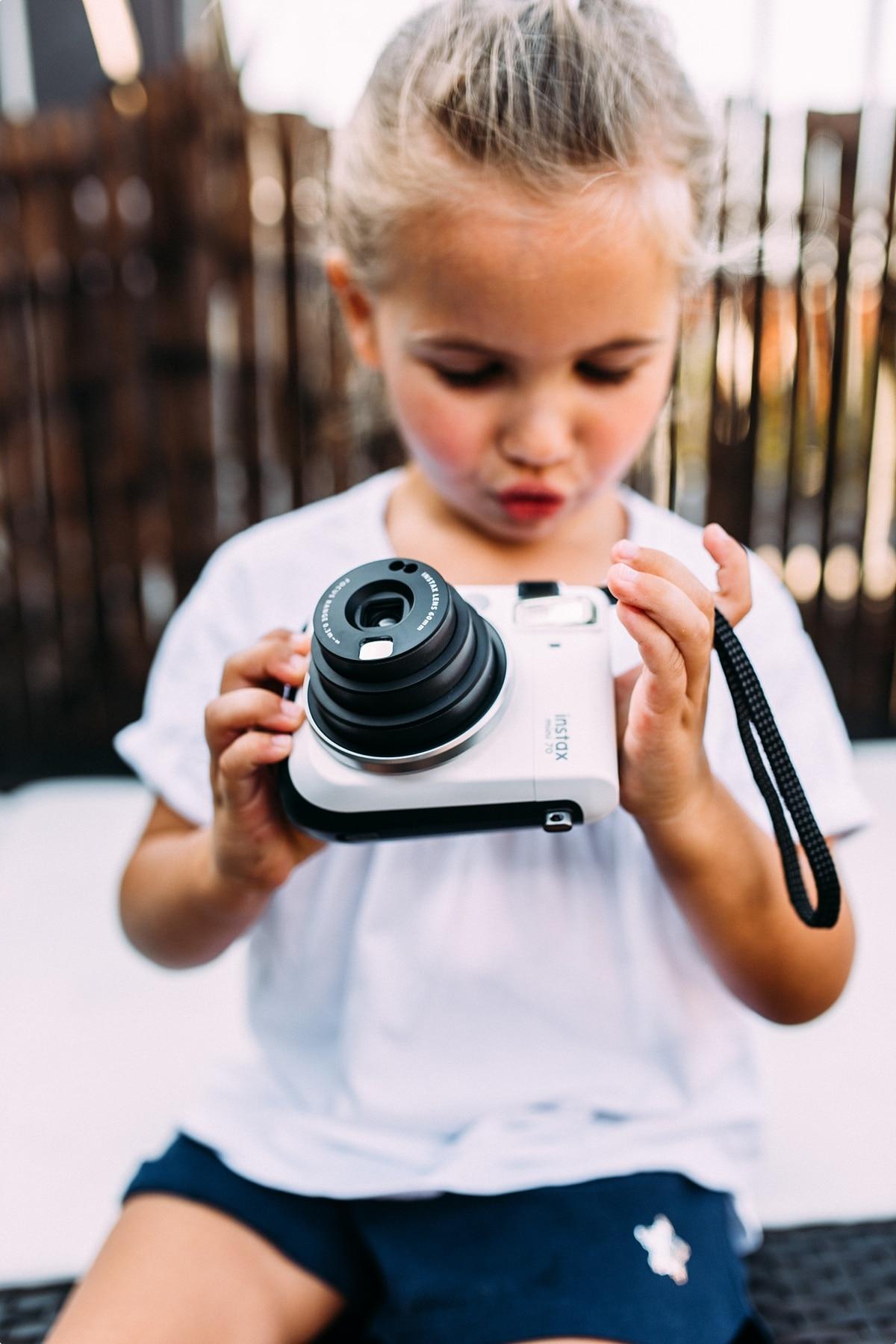 Kleines Mädchen mit Polaroidkamera