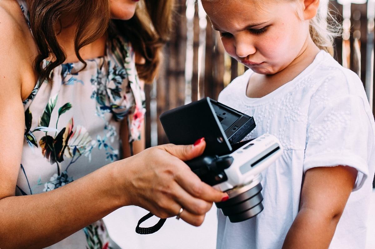 Mama und Tochter inspizieren Kamera