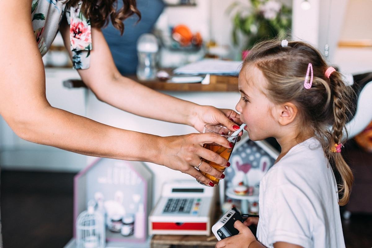 kleines Mädchen mit langen Haaren trinkt zu Hause