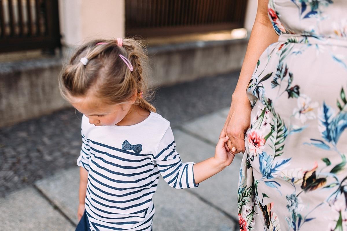 kleine Tochter an der Hand ihrer Mama