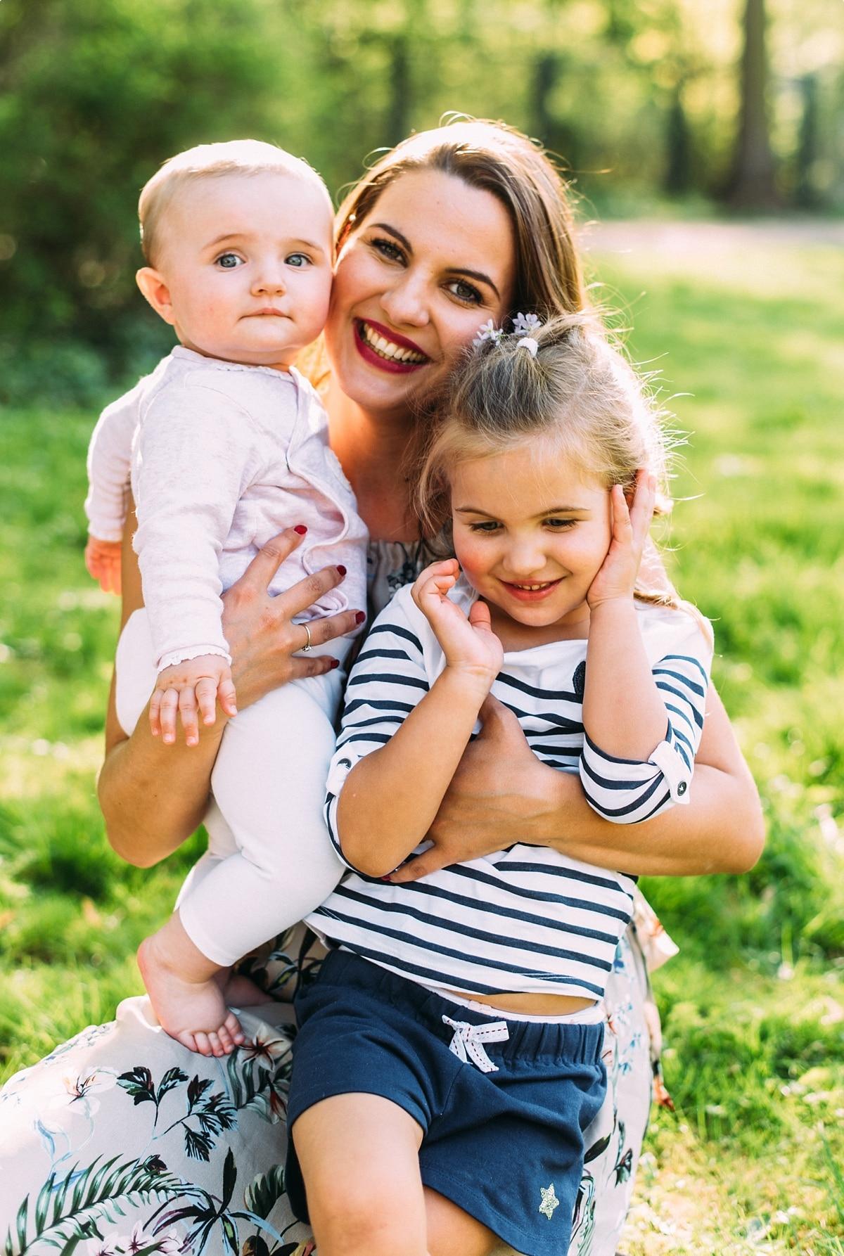 Mama lacht mit ihren beiden Kindern auf einer Wiese