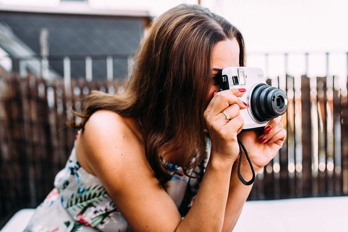 Mama im bunten Kleid und langen Haaren fotografiert mit Polaroid Kamera