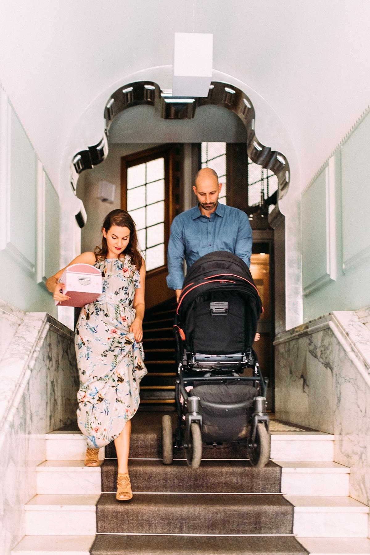 junge Familie mit Kinderwagen im Treppenhaus Altbau