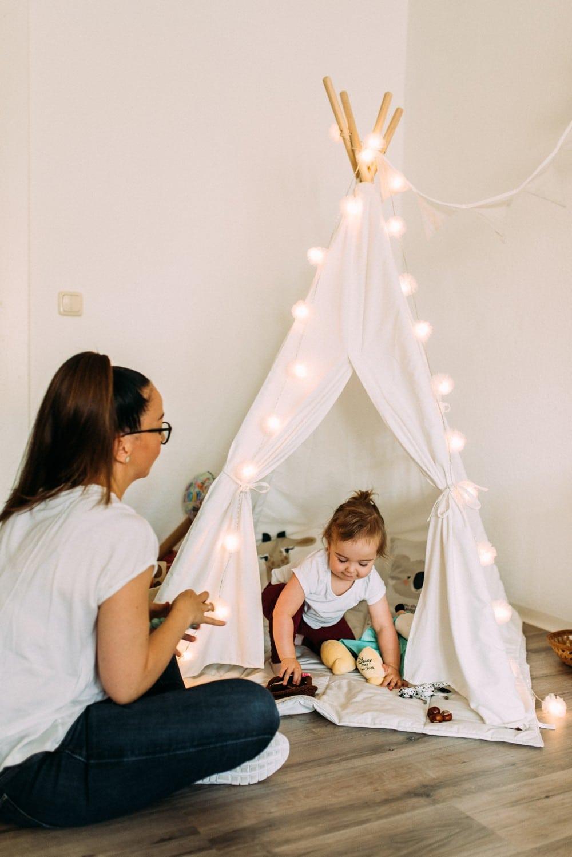 Mama und Tochter spielen im Wohnzimmer mit Tipizelt