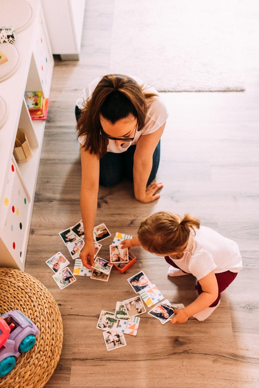 Mama spielt Memory mit ihrer Tochter im Kinderzimmer