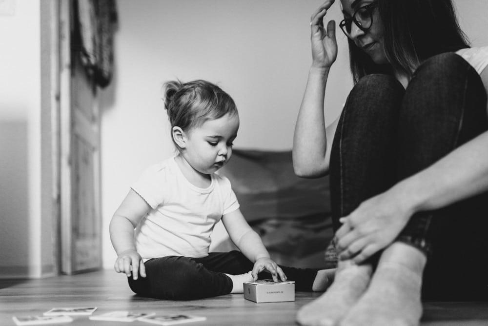 Mama und Tochter spielen Memory auf dem Fußboden schwarz-weiß