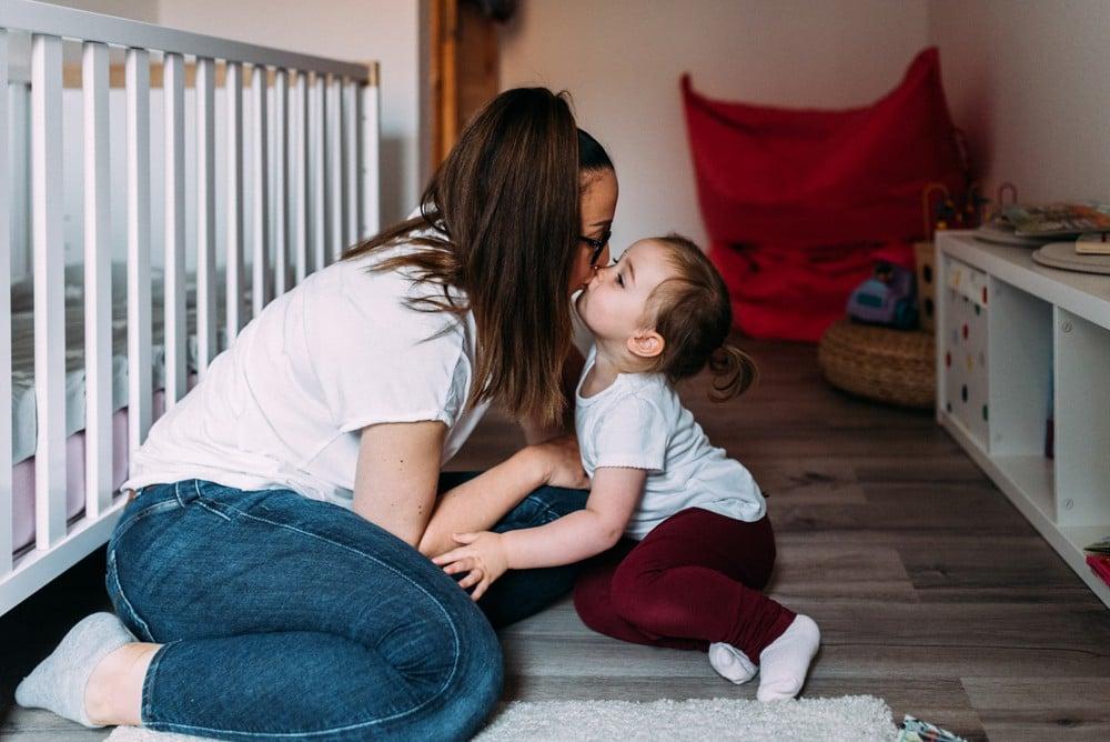 kleine Tochter gibt ihrer Mama einen Kuss