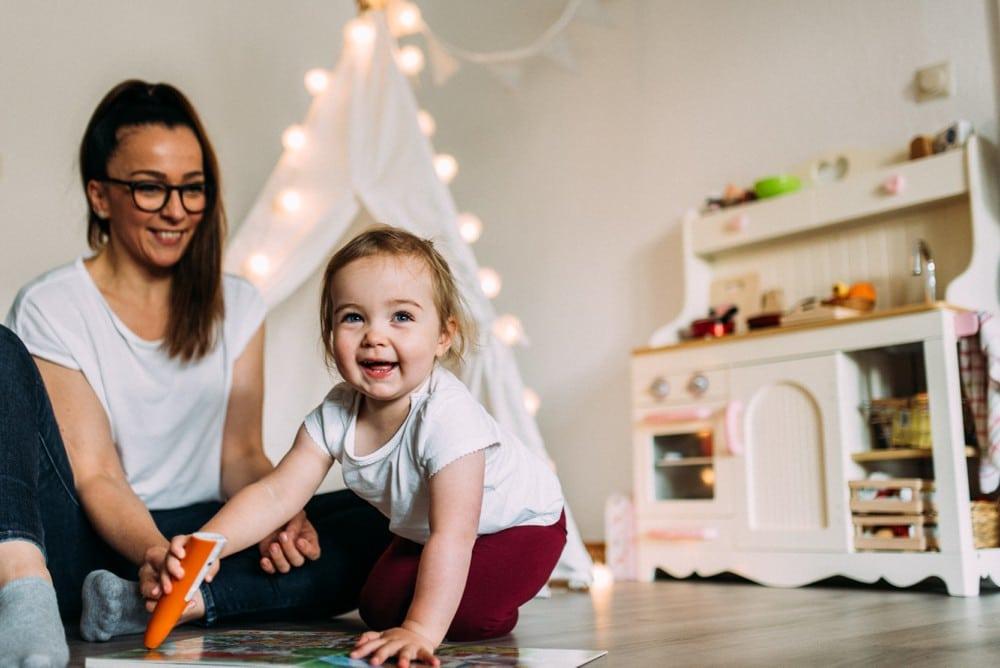 kleines Mädchen spielt im Wohnzimmer mit der Mama