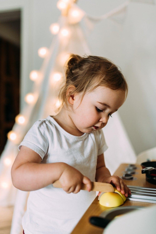 Mädchen mit Zopf spielt mit ihrer Miniküche