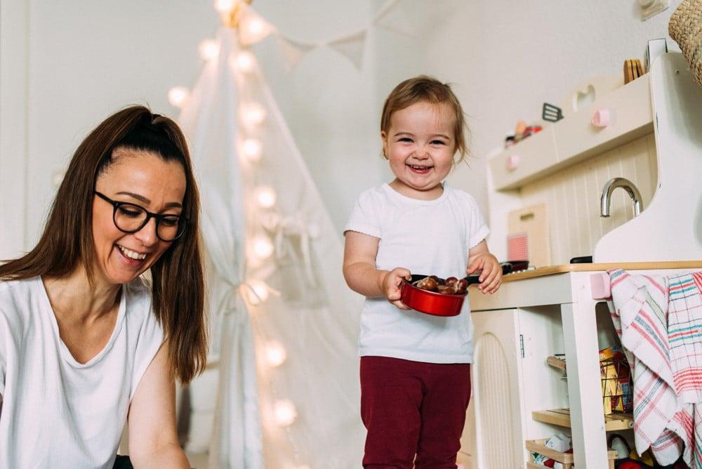 Mama spielt mit Tochter im Wohnzimmer