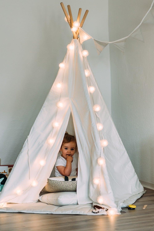 Mädchen steht im beleuchteten Tipizelt im Wohnzimmer
