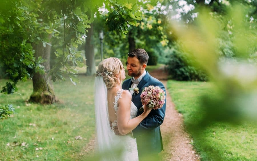 Brautpaar im Grünen mit Brautstrauß