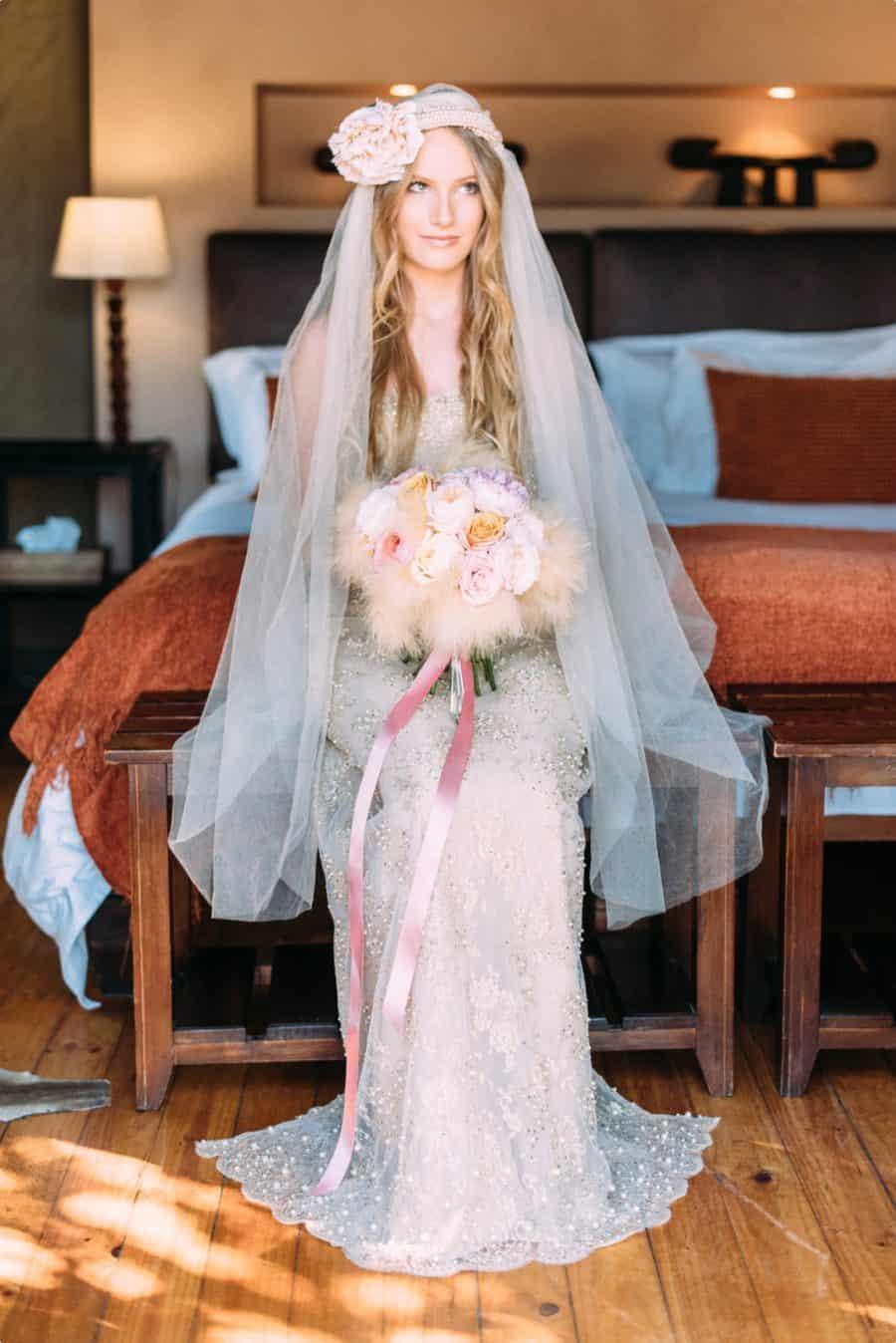 Braut sitz in Traumkleid im Hotelzimmer mit grossem Schleier