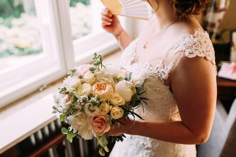 Braut kurz vor der Trauung im Hotelzimmer am Fenster mit Brautstrauß