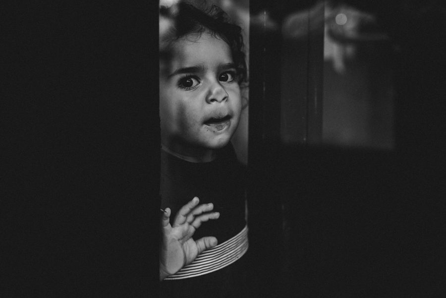Kleines Kind quetscht Mund an die Innenseite der Scheibe