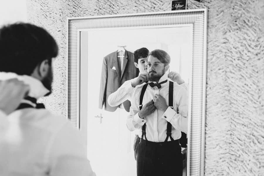 Trauzeuge hilft dem Bräutigam beim Ankleiden