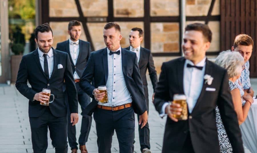 Männer laufen mit Bier in der Hand nebeneinander