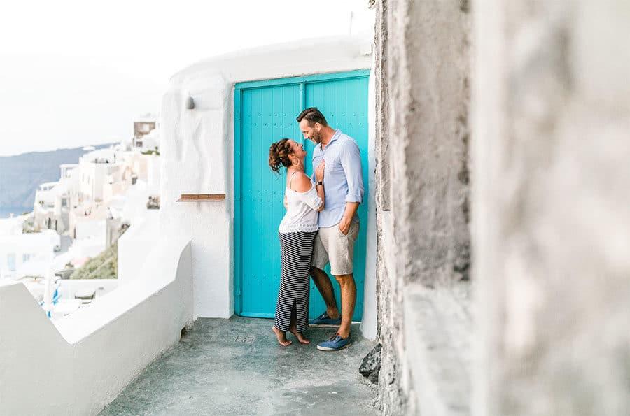 verliebtes Paar an türkisfarbener Tür auf Santorini schauen sich an