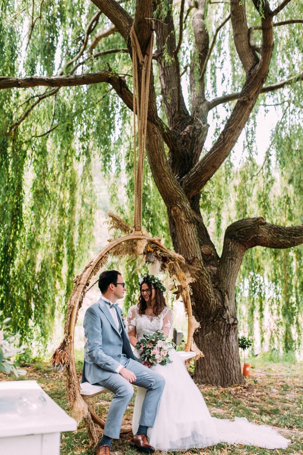 Brautpaar sitzt bei ihrer freien Trauung unter einem Baum auf einer Schaukel und lacht